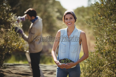 smiling woman carrying olives with man