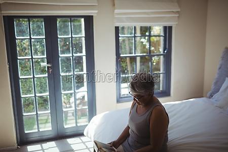 senior woman reading book while sitting