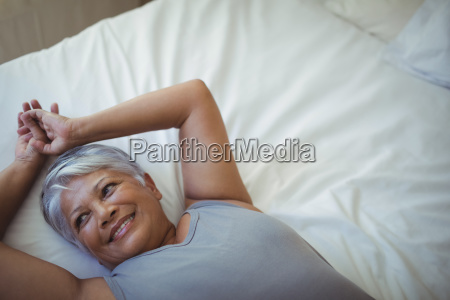 senior woman relaxing on bed in