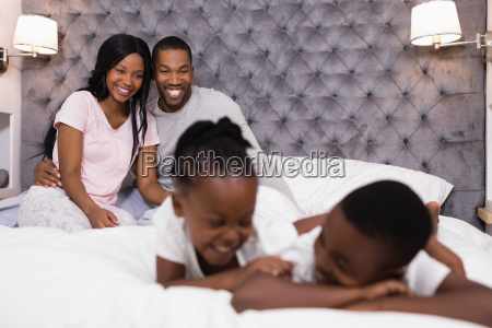 happy couple sitting with children lying