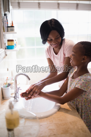 mother looking at daughter while washing