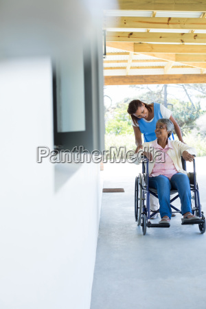 female doctor pushing happy senior patient
