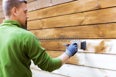 worker painting house exterior with brown