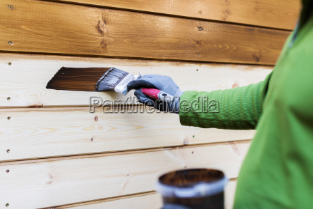 painter with paintbrush painting house facade
