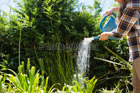 woman watering plants with watering can
