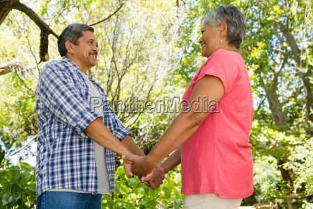 romantic senior couple holding hands in
