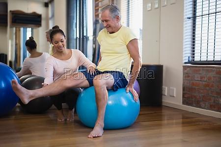 female therapist helping senior male patient