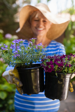 smiling senior woman holding fresh flower