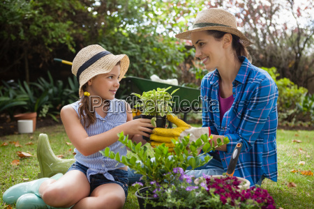 smiling daughter and mother with potted