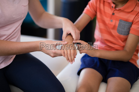 midsection of female therapist examining hand