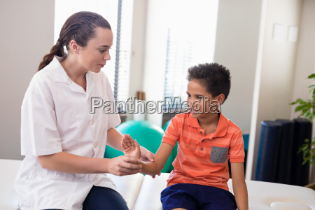 young female therapist examining hand of