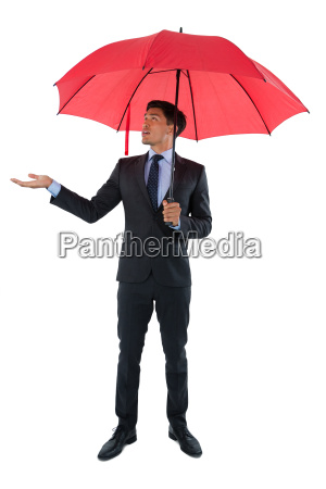 full length of businessman holding umbrella