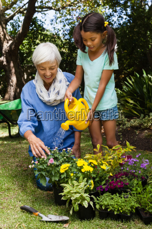 senior woman looking at girl watering
