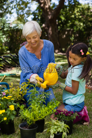 smiling senior woman and girl watering