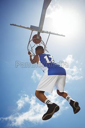 rueckansicht des maennlichen teenager haengen basketballkorb