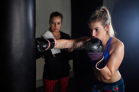 trainer der frau im boxen unterstuetzt