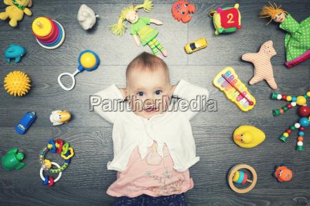 nettes baby mit vielen spielwaren auf