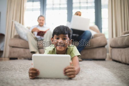 portrait of boy holding digital tablet