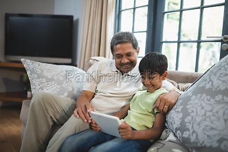 smiling junge mit grossvater mit digitalen