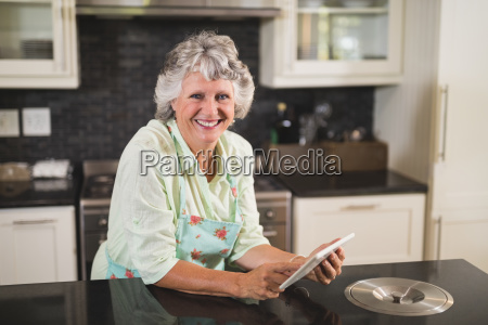portrait of smiling senior woman using