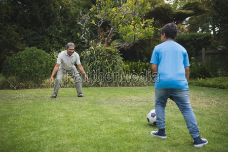 boy playing soccer with grandfather at