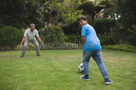 happy boy playing soccer with grandfather