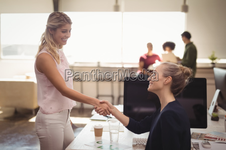 female business people shaking hands at
