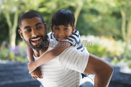 happy father piggybacking son at porch
