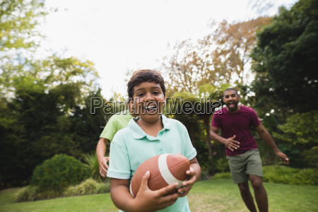 boy playing rugby with father and
