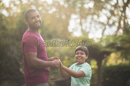 cheerful father and son playing at