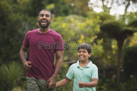 cheerful father and son holding hands