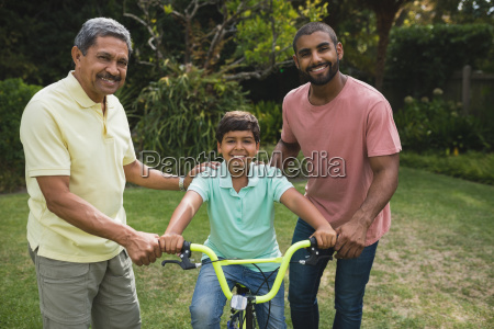 father and grandfather helping boy while