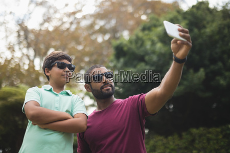 father taking selfie with son at