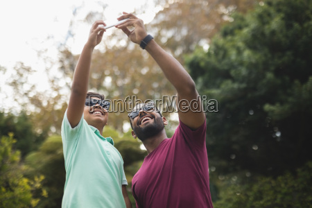 cheerful father taking selfie with son