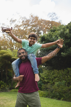 cheerful father piggybacking son at park