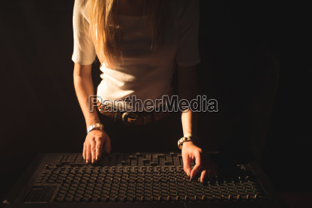 mid section of female dj operating
