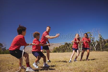 kinder spielen tauziehen waehrend hindernisparcours