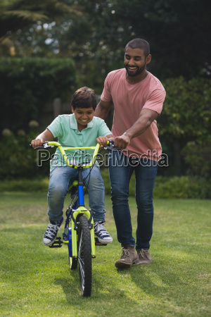 father assisting son while riding bicycle