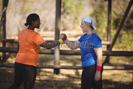 happy friend holding hands during obstacle