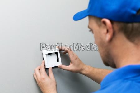 electrician in blue uniform installing light