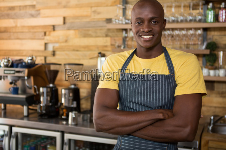 male barista standing arms crossed in