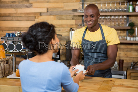 male barista serving coffee to customer