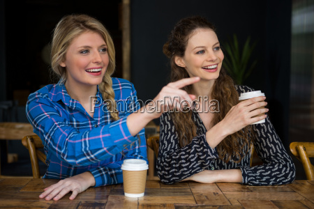 smiling woman showing something to friend