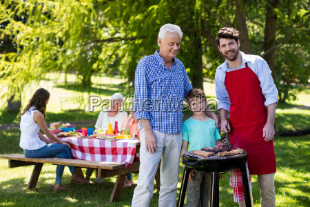 grandfather father and son barbequing in
