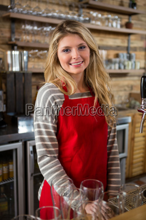 smiling young female barista at counter