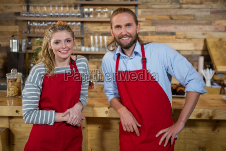 smiling male and female baristas at