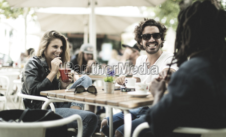 two men and woman sitting outdoors