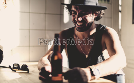 bearded man wearing hat sitting indoors