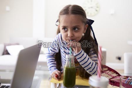 portrait of little girl drinking green