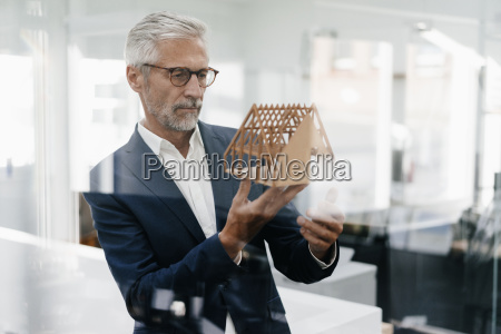 mature businessman examining architectural model in